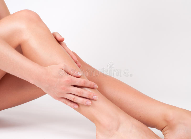 Hair removal and epilation. Woman legs with smooth skin after depilation. Long woman legs with smooth skin after depilation. Female hand touching perfect royalty free stock photo