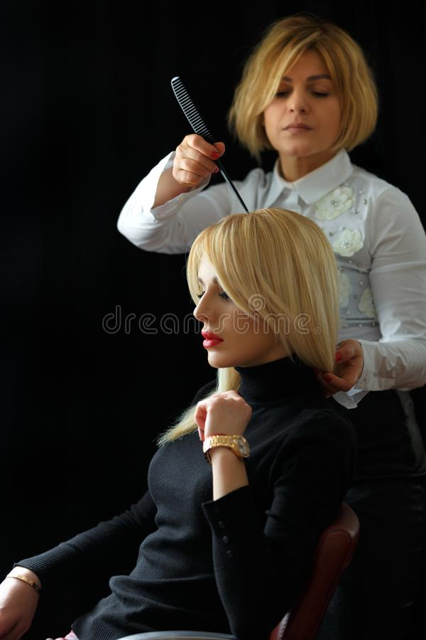 Hair salon. Woman hairstyle. Hairdresser combing hair of client. royalty free stock photography