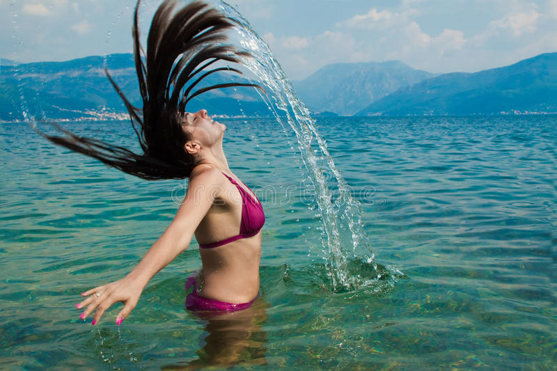 Hair splash. Young, attractive woman, having fun in the water, straying her head back, letting it splash some water. Shot to capture the movement and freeze the royalty free stock image