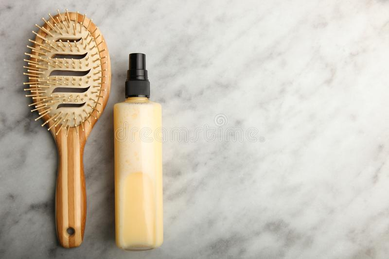 Hair spray and a comb. Lie on a marble background. Top view, copy space royalty free stock photography