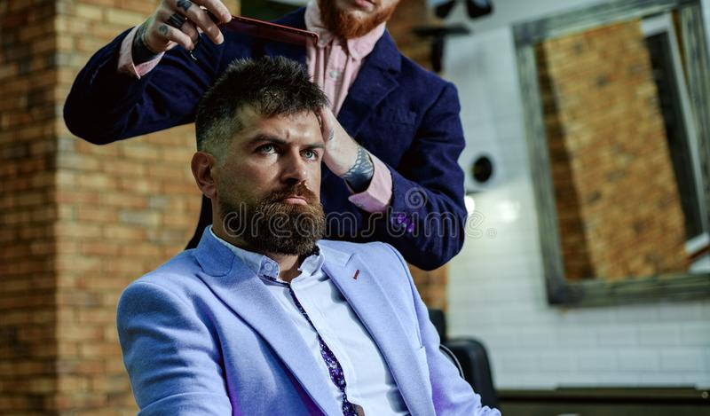 Hair style and hair stylist. Barber making haircut of attractive bearded man in barber shop. Shaving man and razor man royalty free stock image