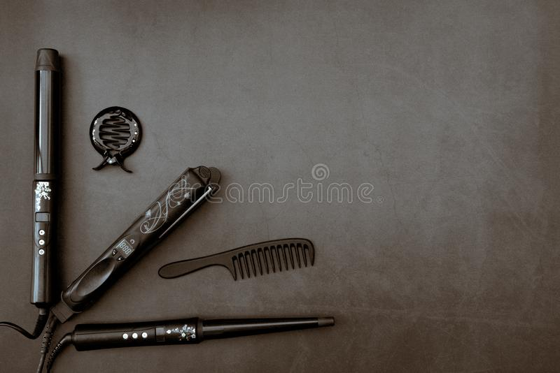 Hair styling accesories in black, grey background. Black hair styling accesories with flower pattern on dark grey background royalty free stock photography