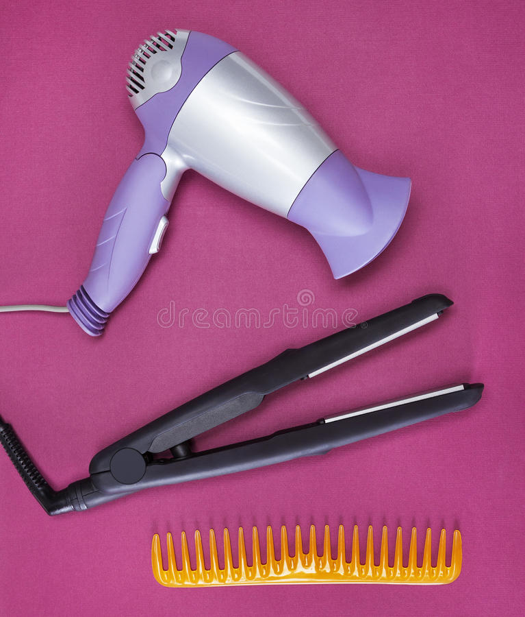 Hair styling appliances and accessories. Hair styling iron, hairdryer and wide tooth comb on vinous textured surface. Appliances and accessories to create royalty free stock images