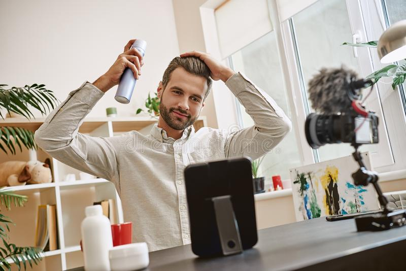 Hair styling. Cheerful male beauty blogger recording video blog episode about new hair spray. Youtube. Beauty. Content royalty free stock image