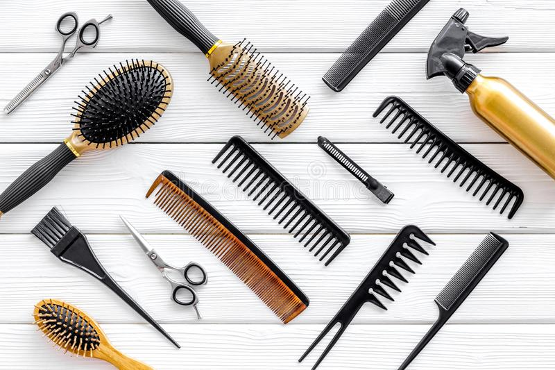 Combs, spray and hairdresser tools in beauty salon work desk on white wooden background top view pattern. Hair styling concept. Combs, spray and hairdresser stock photos