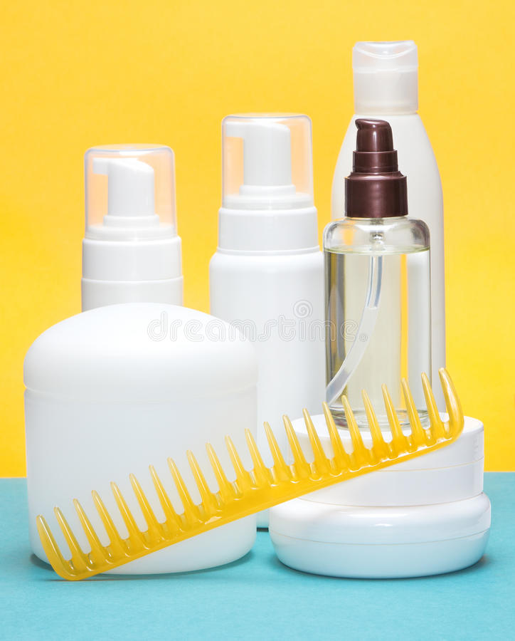 Hair styling products. Different hair styling products with wide tooth comb on blue and yellow bright background stock photo