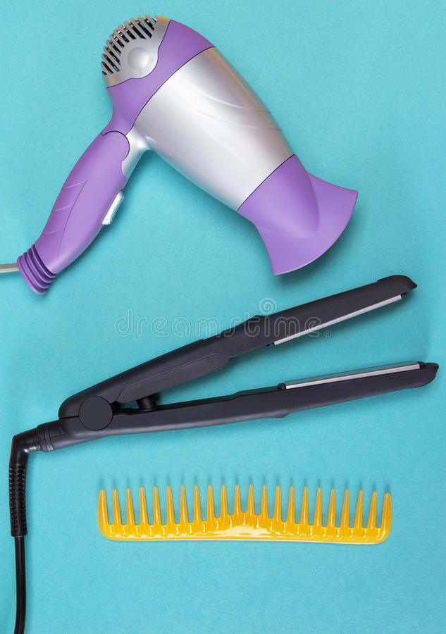 Hair styling tools and accessories. Hair styling iron, hairdryer and wide tooth comb on blue background. Tools and accessories to create beautiful hairdo stock photos
