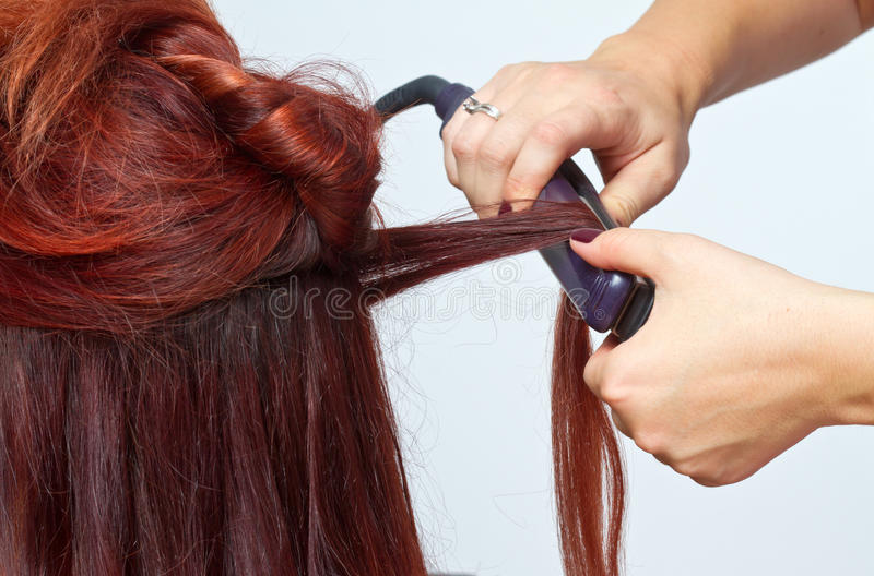 Hair styling. Woman having her hair straighten with a hair styling tool stock photography