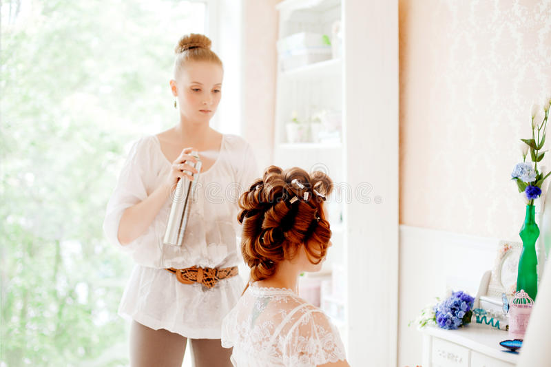 Hair stylist makes the bride on the wedding day stock image