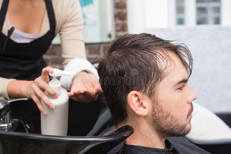 Hair stylist putting conditioner in mans hair royalty free stock images