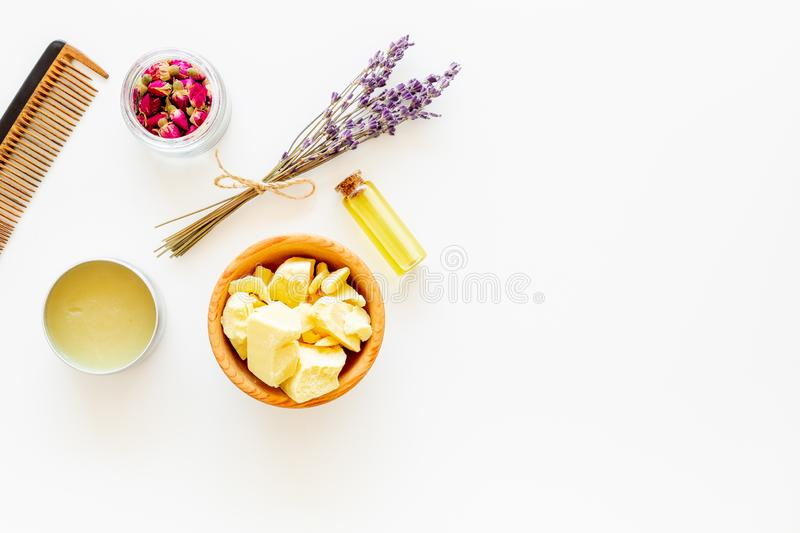 Hair treatment with natural products. Jojoba, argan, coconut oil near bunch of lavender and hairbrush on white royalty free stock photo