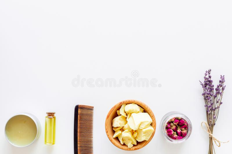 Hair treatment with natural products. Jojoba, argan, coconut oil near bunch of lavender and hairbrush on white royalty free stock images