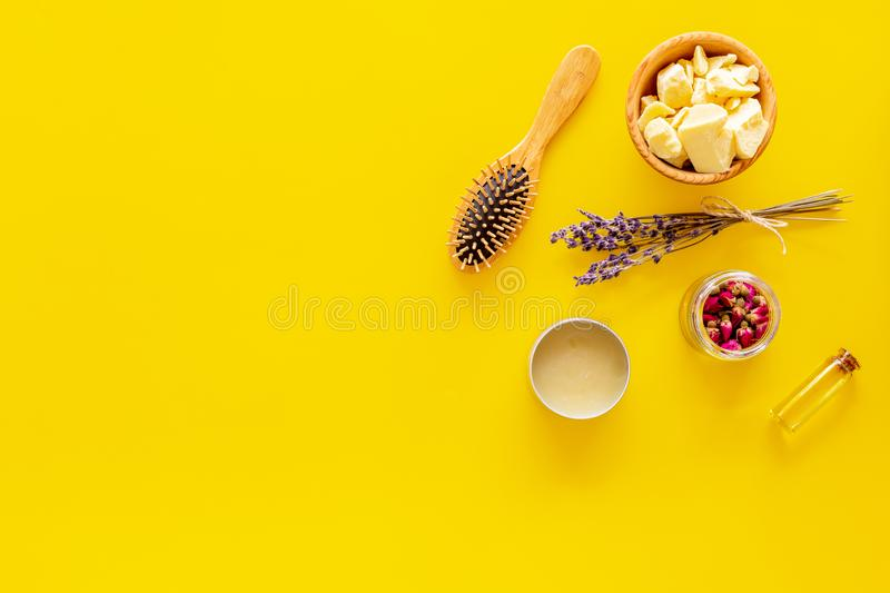 Hair treatment with natural products. Jojoba, argan, coconut oil near bunch of lavender and hairbrush on yellow stock photography