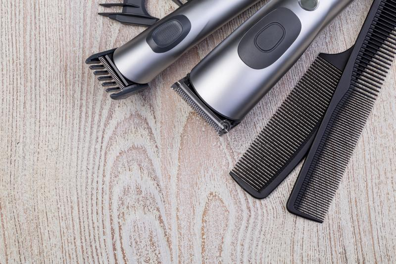 Hair trimmer with comb. On wooden background royalty free stock image