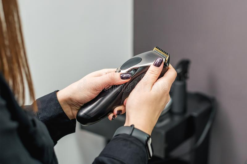 Hair trimmer machine for hairstyles in the hands of hairdresser. Woman`s hands holds a hair clipper machine on the background of a hairdresser salon royalty free stock photography