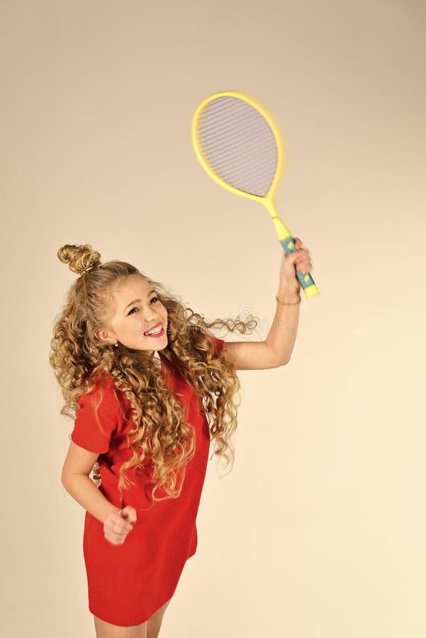 haircare Übendes Tennis Vorbereiten zum großen Spiel wenig Mädchen des blonden Haares im roten Kleidergriff-Tennisschläger tennis lizenzfreies stockbild