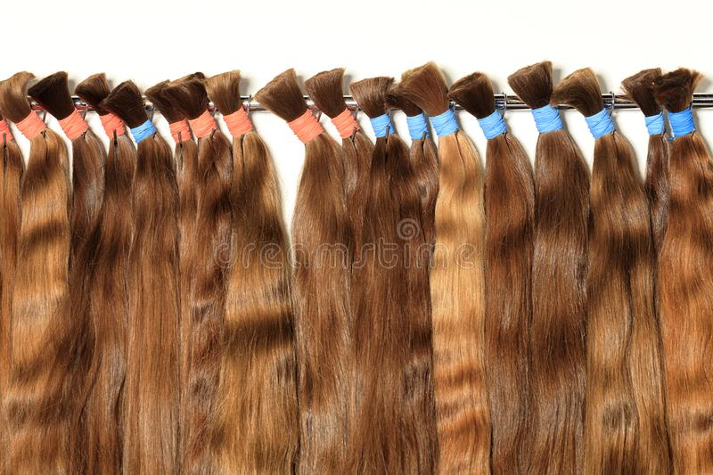 Natural, chocolate color, brown, shiny bundles of healthy hair extensions. Haircare female hair, technology, style and beauty concept. Natural chocolate colored royalty free stock photos
