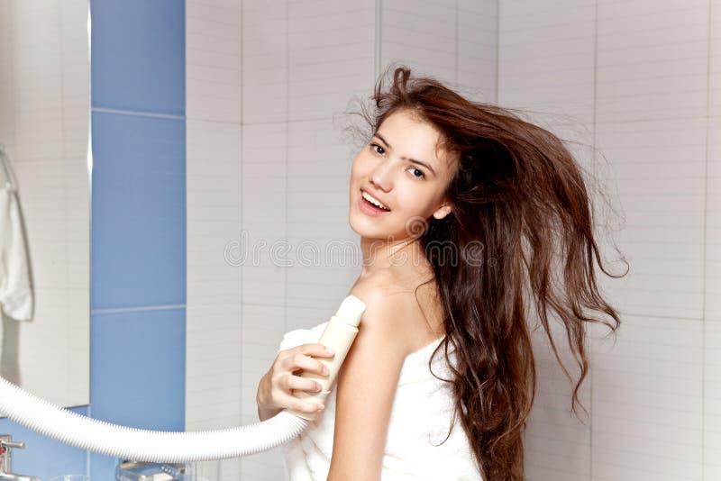 haircare Mooi langharige vrouwen drogend haar in badkamers royalty-vrije stock afbeelding