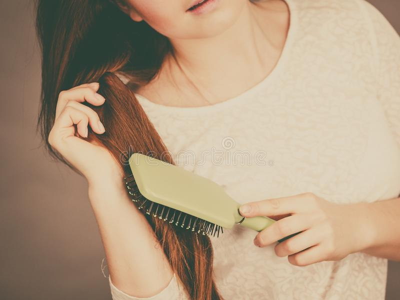 Happy woman brushing her hair. Haircare and morning hairstyling concept. Happy woman brushing her long dark brown hair royalty free stock image