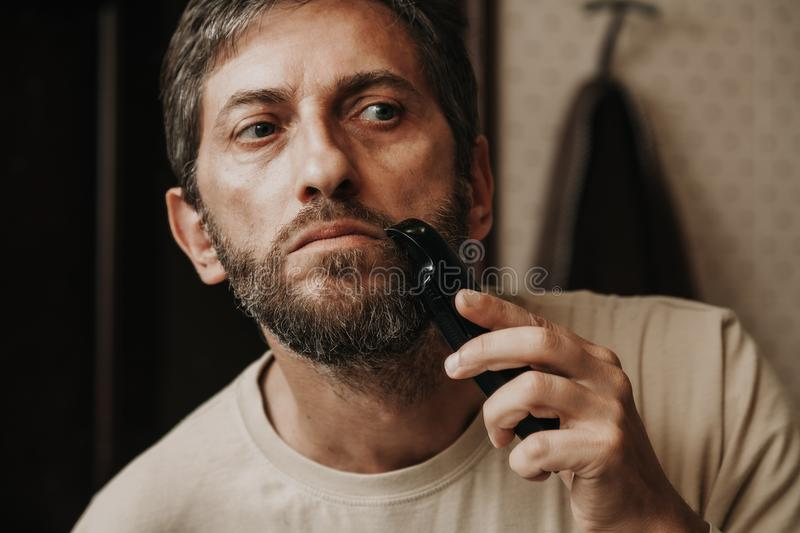 Cutting mustache with black trimmer close-up. Haircut beard trimmer. A man cuts his mustache with a machine royalty free stock photos