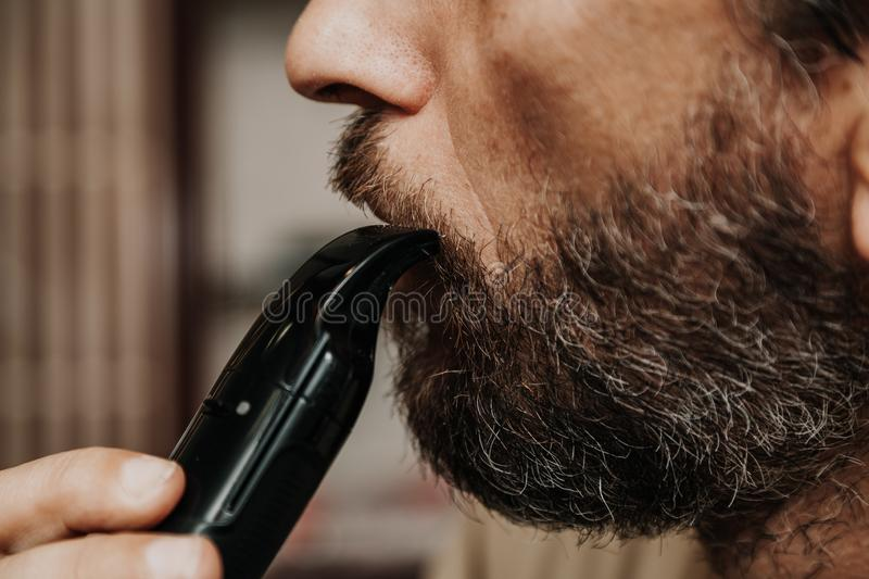 Cutting mustache with black trimmer close-up. Haircut beard trimmer. A man cuts his mustache with a machine royalty free stock photography