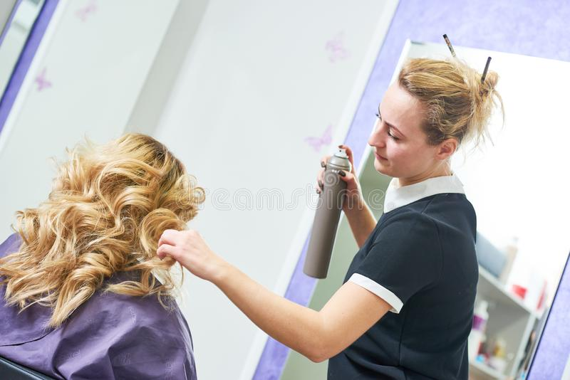 Hairdo in beauty salon. hairdresser fixing hair with hairspray stock photos