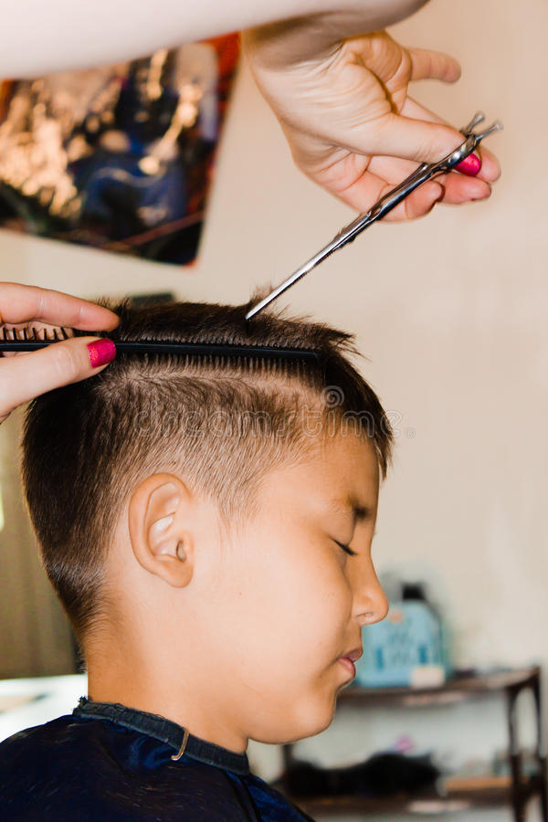 Haircut in a hair studio. Hairdressers cuts boy's hair with hairclipper stock photo