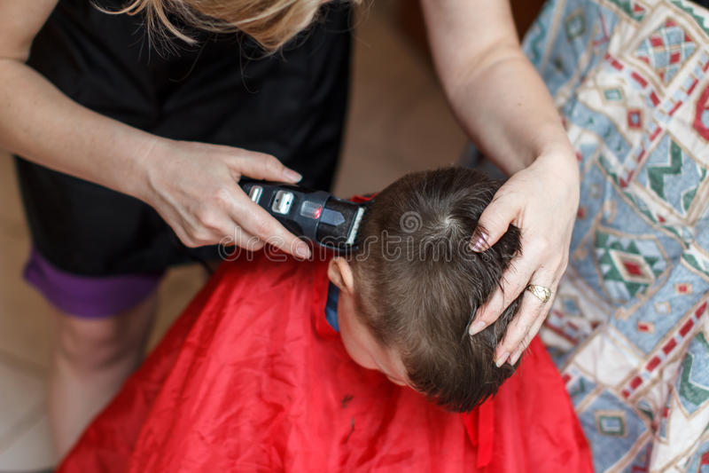 Haircut of little boy with machine. Haircut for boy at home with machine royalty free stock photo
