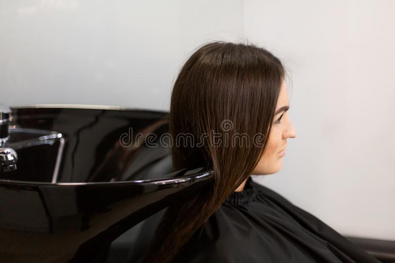 Haircut master washes hair of her client`s had royalty free stock photography