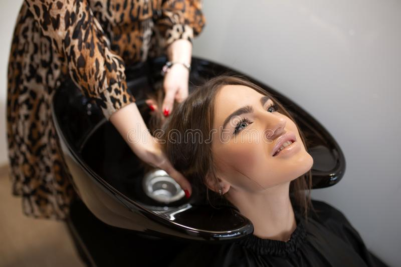 Haircut master washes hair of her client`s had stock photography