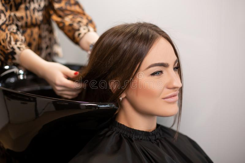 Haircut master washes hair of her client`s had stock images