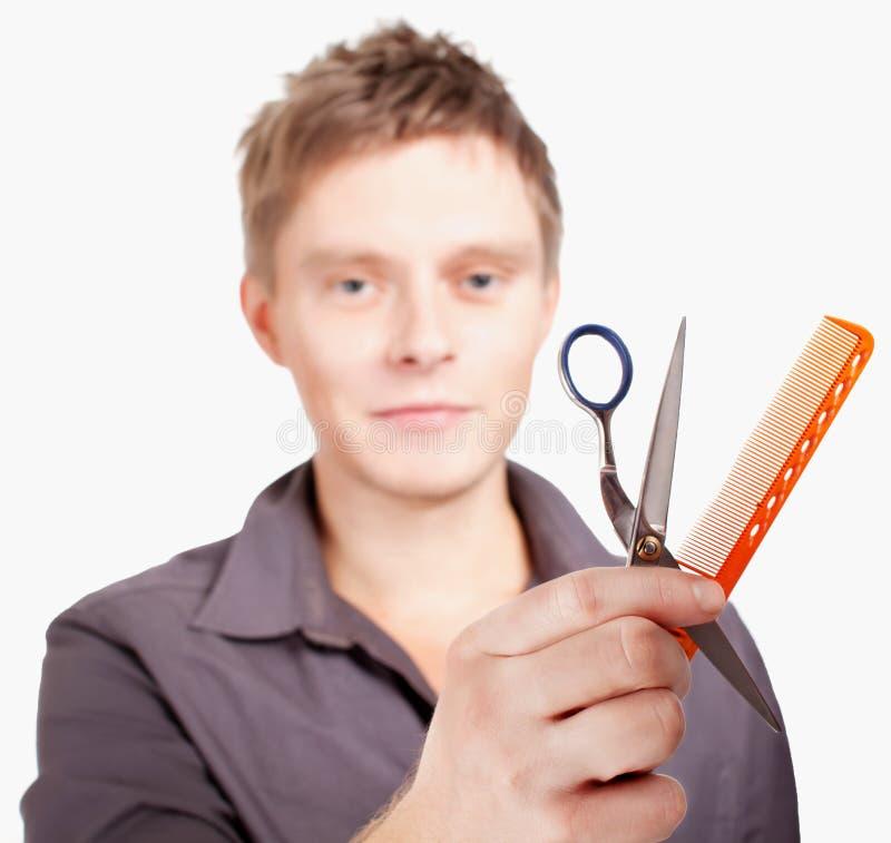 Haircutter elegante joven que sostiene las tijeras y el cepillo. imagen de archivo libre de regalías