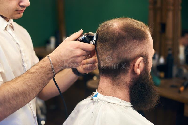 Haircutting curto masculino profissional para o cliente farpado no barbeiro Barbeiro novo que trabalha com l?mina el?trica Fim ac fotografia de stock royalty free