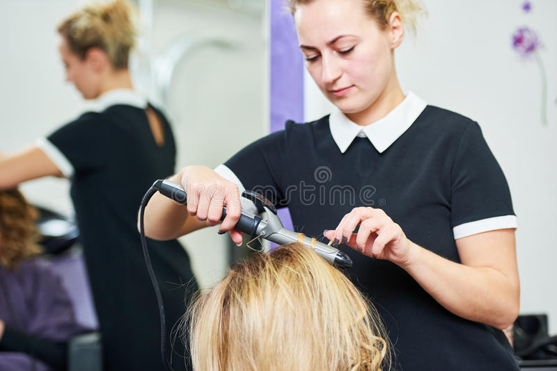 Hairdo in beauty salon. hairdresser making coiffure with curl to wonam stock photography