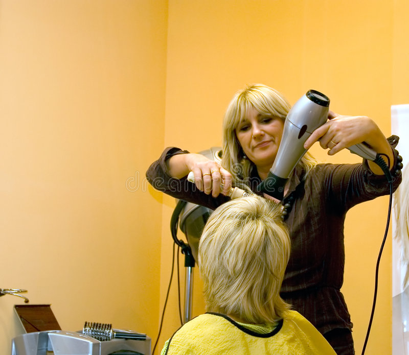 At the hairdresser. Blond hairdresser with her client, hairdryer and brush in action, orange walls as copy space