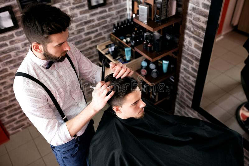 Hairdresser adjusts hair a customer with a comb stock image