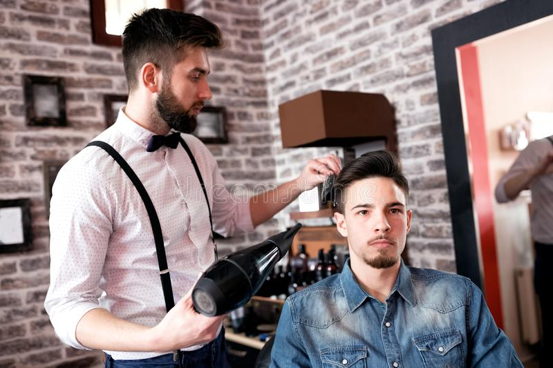 Hairdresser adjusts hair a customer with a comb stock photography