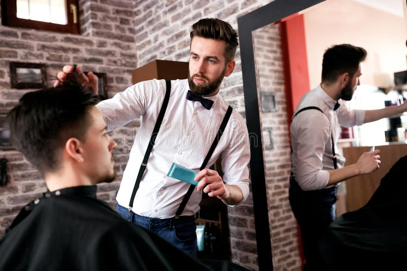 Hairdresser adjusts hair a customer with a gel royalty free stock images