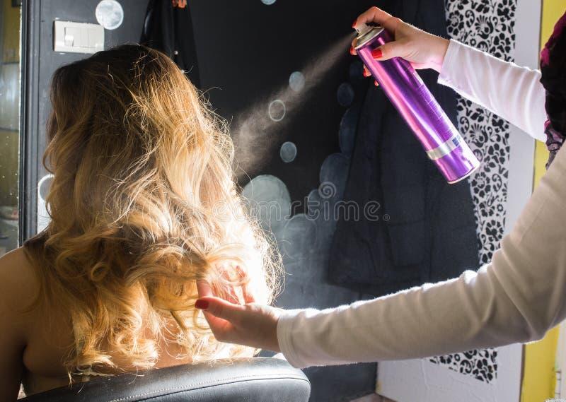 Hairdresser applying hair spray on ombre hair. In beauty salon stock photos