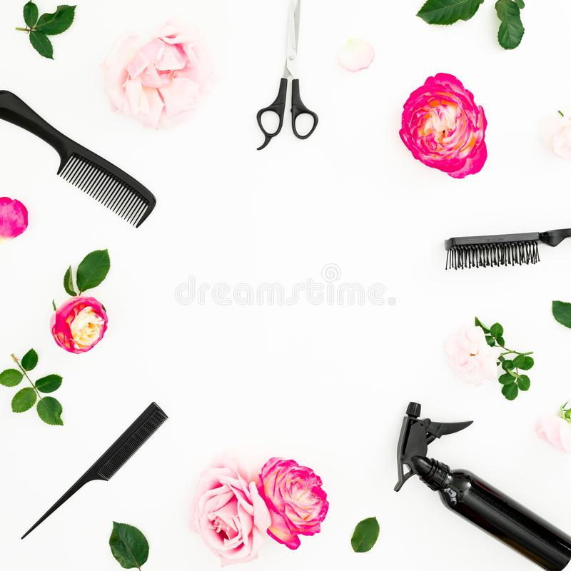 Hairdresser beauty concept with spray, scissors, combs and roses flowers on white background with copy space. Flat lay, top view royalty free stock image