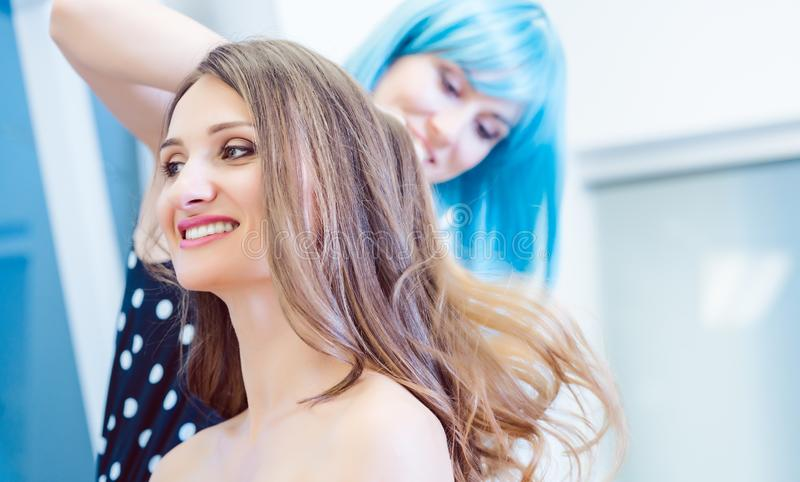 Hairdresser fixing hair of customer woman with spray. Hairdresser with blue wig fixing hair of customer women with spray stock images