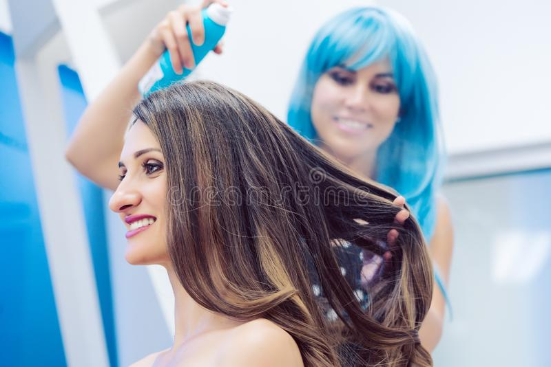 Hairdresser fixing hair of customer woman with spray. Hairdresser with blue wig fixing hair of customer women with spray stock photo