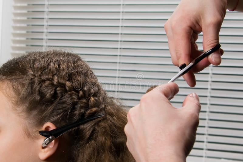 The hairdresser braids the pigtail to the child and cuts the ends of the hair, with scissors stock image