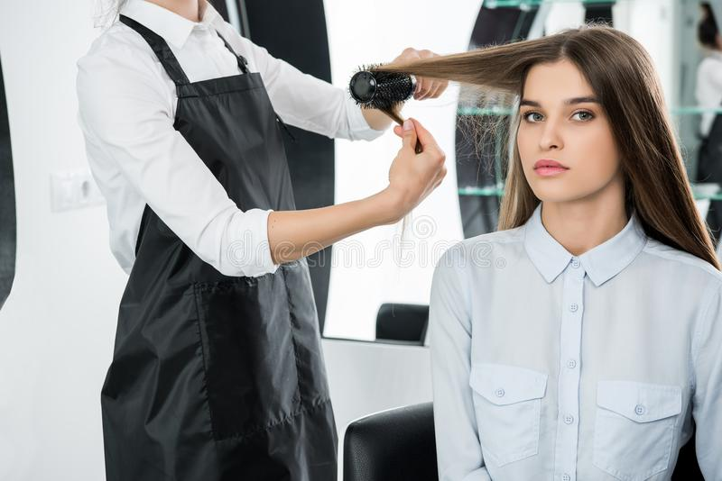 Hairdresser brushing hair of woman. Hairdresser brushing hair of attractive young woman in beauty salon royalty free stock images