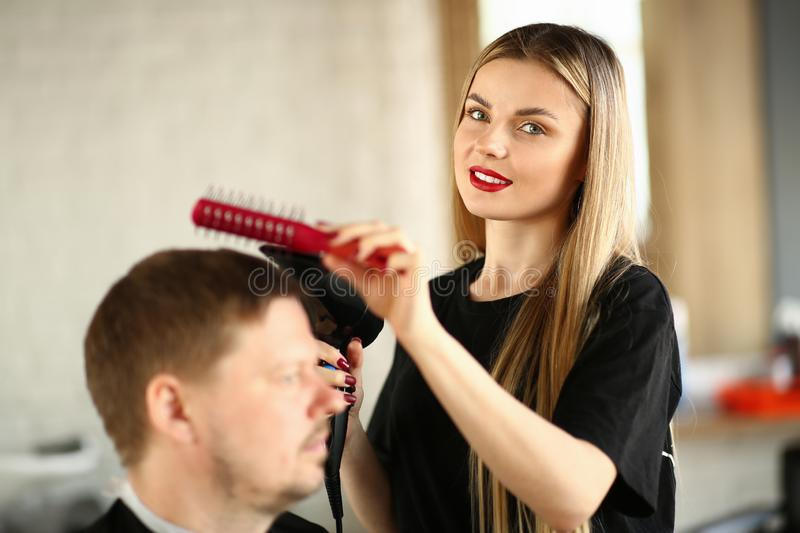 Hairdresser Combing Male Hair and Blowing by Dryer. Young Hairstylist Drying Man Haircut. Woman Beautician Styling Hairdo for Guy Sitting in Beauty Salon stock photo