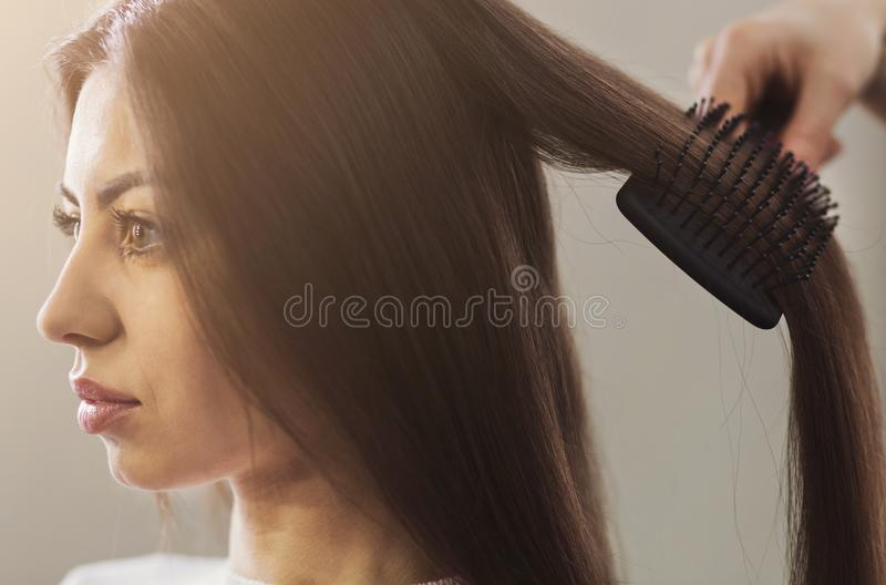 Hairdresser combing woman hair in a professional salon royalty free stock photo