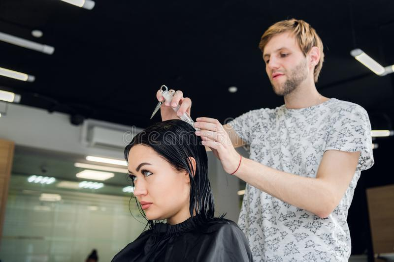Hairdresser creating a hairstyle for beautiful woman closeup royalty free stock photography