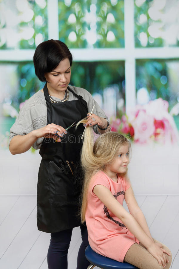 Hairdresser cuts girl long hair royalty free stock photography