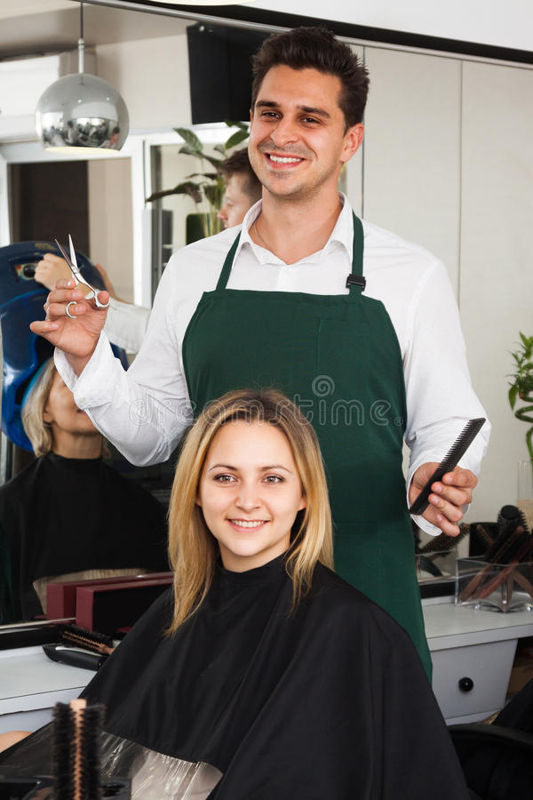 Hairdresser cuts hair of blonde girl at salon royalty free stock image