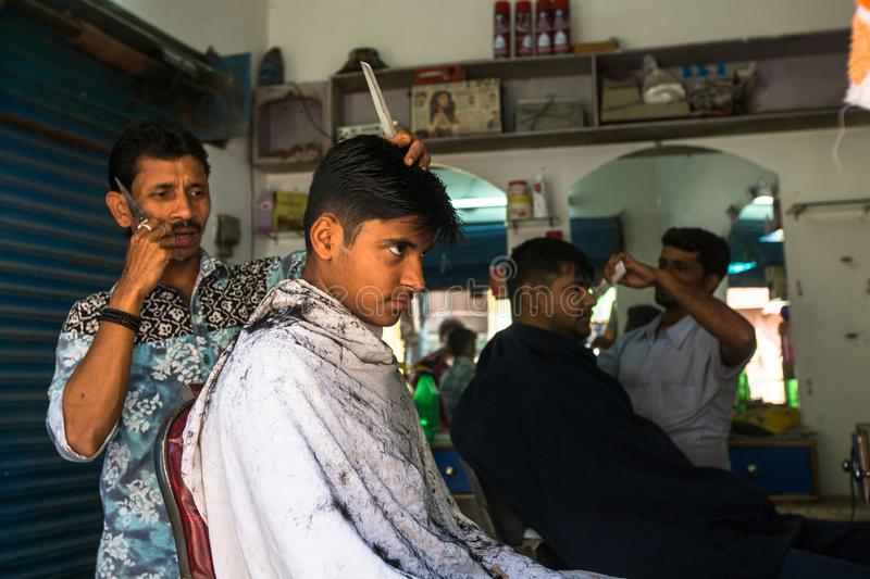 Hairdresser cuts hair of the pilgrim. VARANASI, INDIA - MAR 14, 2018: Hairdresser cuts hair of the pilgrim. A haircut in Varanasi is considered to be a kind of stock image